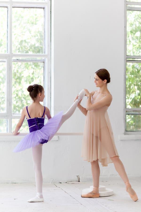 La pequeña bailarina que presenta en la barra del ballet con fotografía de archivo libre de regalías