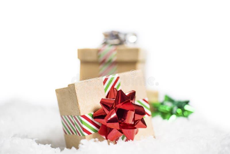 La pequeña caja de regalo con la cinta rayada y el día de fiesta brillante arquean sentarse foto de archivo libre de regalías