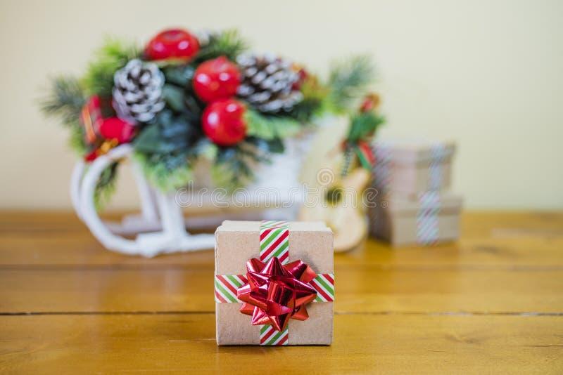 La pequeña caja de regalo envuelta en cinta rayada y el día de fiesta brillante arquean o fotografía de archivo