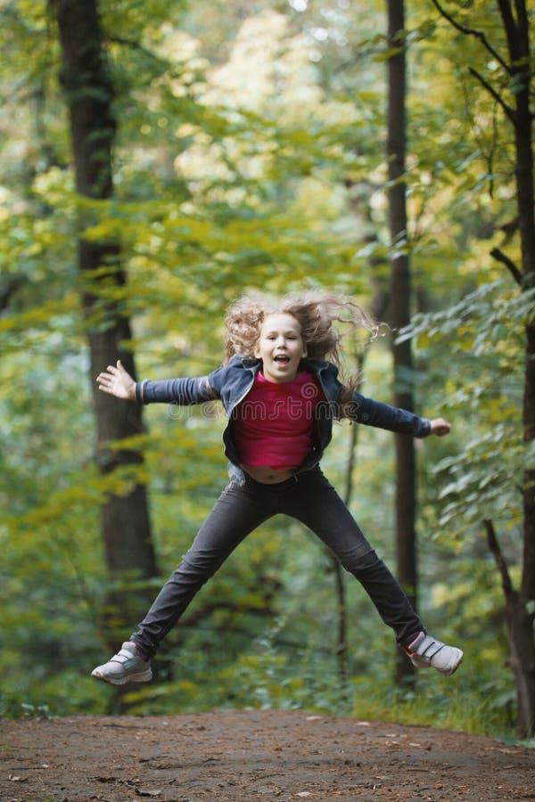 La pequeña chaqueta sonriente de los vaqueros del niño de la muchacha que lleva - está saltando en parque fotografía de archivo
