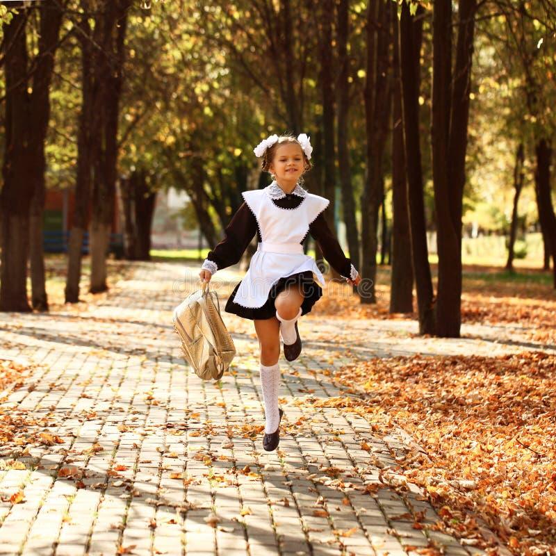 La pequeña colegiala feliz va a casa de escuela imagenes de archivo