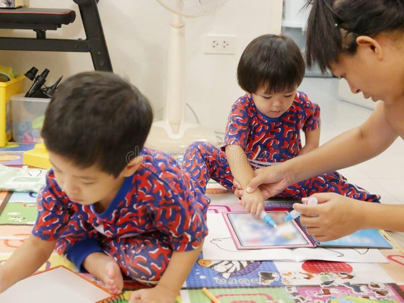 La pequeña derecha asiática del bebé que es enseñada por su madre para sostener una pluma del color para hacer la pintura foto de archivo libre de regalías