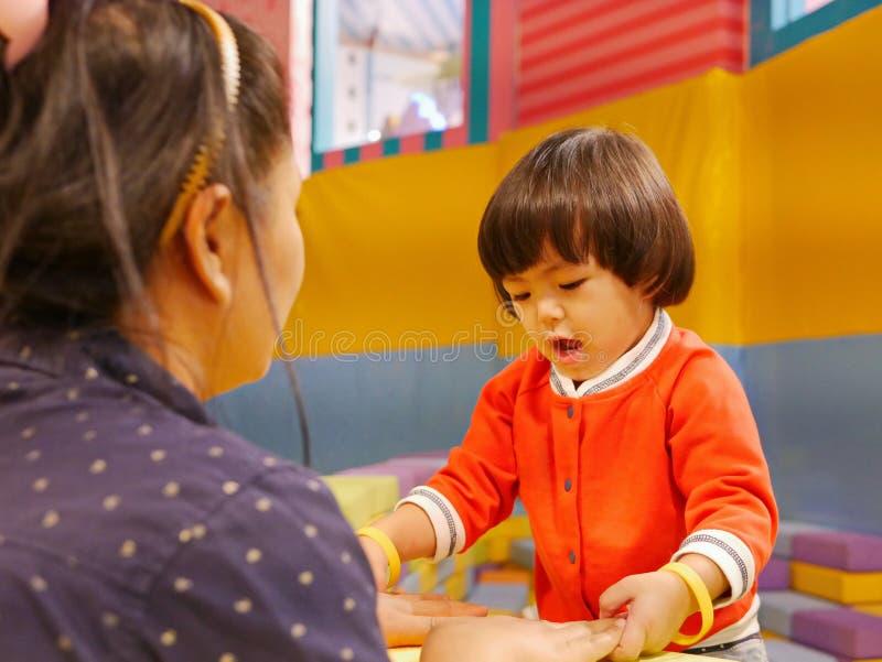 La pequeña elevación/que quita del bebé las manos de su madre lejos de los ladrillos/la bloquea de la espuma el jugar, rechazando fotografía de archivo libre de regalías