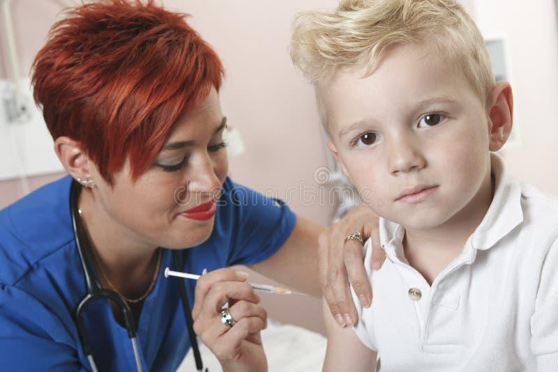 La pequeña enfermera del muchacho le da un tiro imagen de archivo