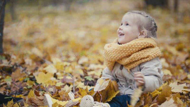 La pequeña hija con su madre juega con las hojas amarillas en parque del otoño - la muchacha es feliz y risa fotografía de archivo