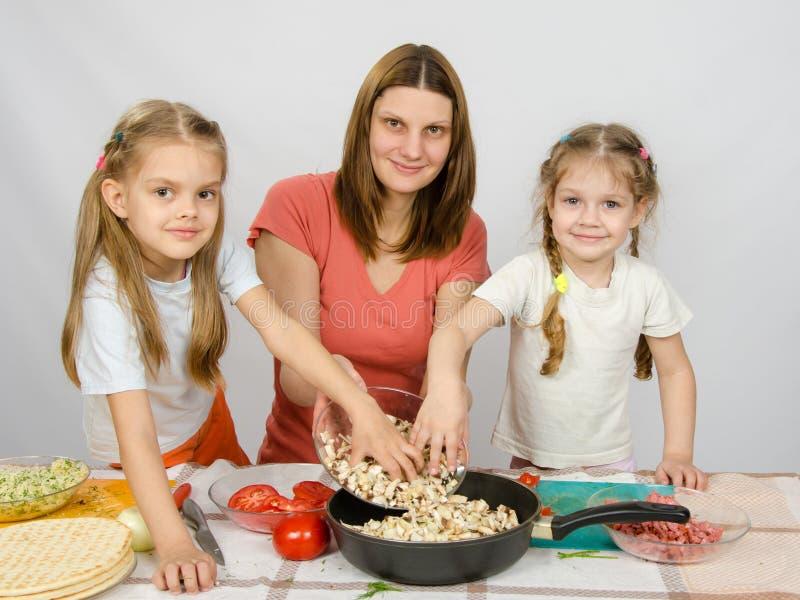 La pequeña hija dos en la tabla de cocina que ayuda a su madre vierte setas tajadas de la placa a la cacerola imágenes de archivo libres de regalías