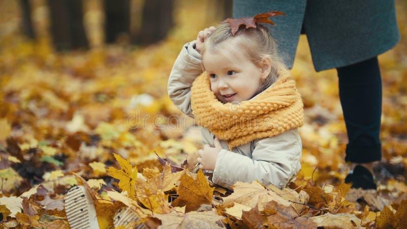 La pequeña hija juega con las hojas amarillas en el parque del otoño - la muchacha es feliz y de risa - granangular foto de archivo libre de regalías