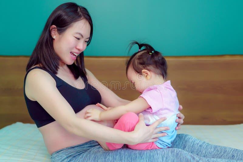 La pequeña hija que se sienta en la madre asiática hermosa de la señora del revestimiento A de la madre está embarazada feliz imágenes de archivo libres de regalías