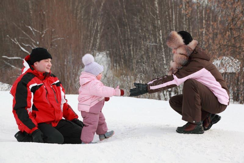 La pequeña hija va de padre a la madre en la nieve fotos de archivo
