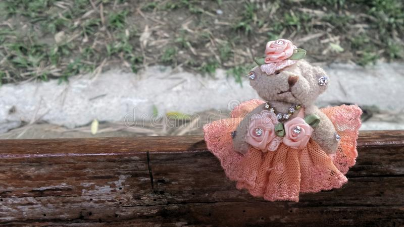 La pequeña muñeca linda del oso en la situación vening del vestido de la víspera anaranjada se sienta en el banco de madera ning  imagen de archivo libre de regalías
