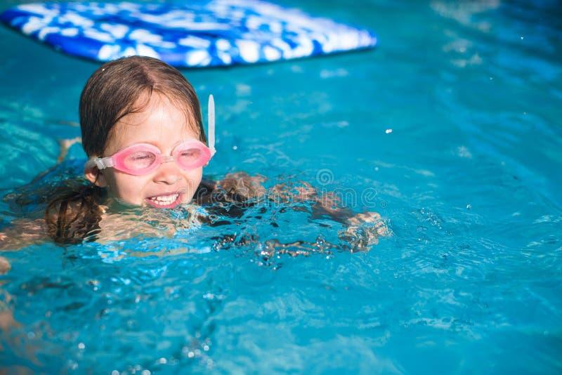 La pequeña muchacha adorable goza en la piscina imagenes de archivo