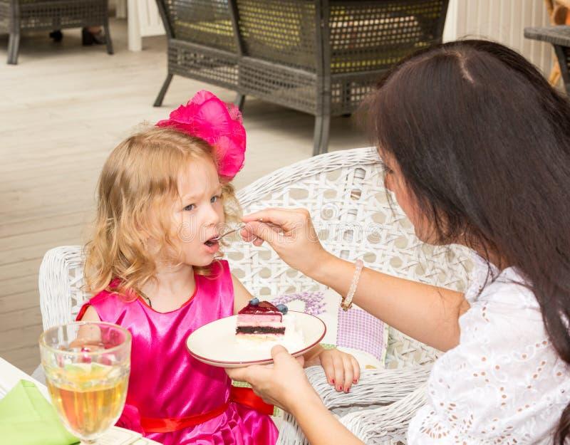 La pequeña muchacha adorable que celebra 3 años de cumpleaños y come la torta imagen de archivo