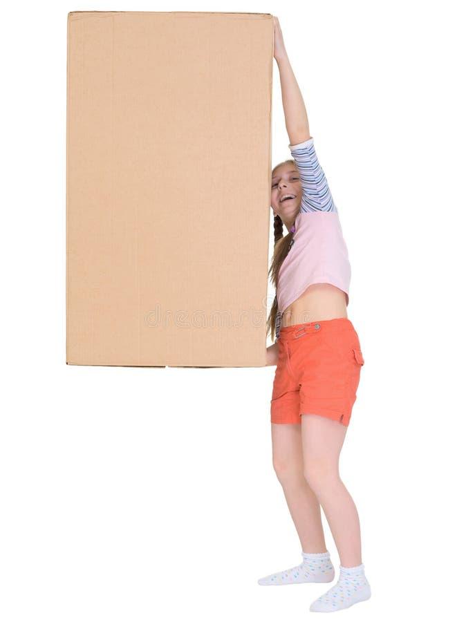 La pequeña muchacha alegre arrastra la caja de cartón grande imagen de archivo