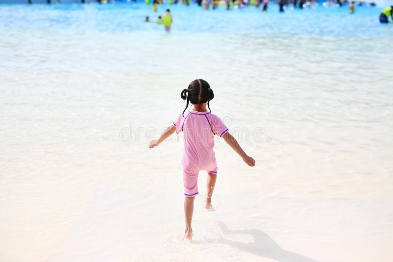 La pequeña muchacha asiática del niño goza y funcionamiento en la piscina grande al aire libre el días de fiesta Niños de la vist imagen de archivo libre de regalías
