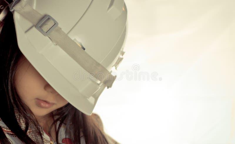 La pequeña muchacha asiática está llevando el sombrero de protección imágenes de archivo libres de regalías