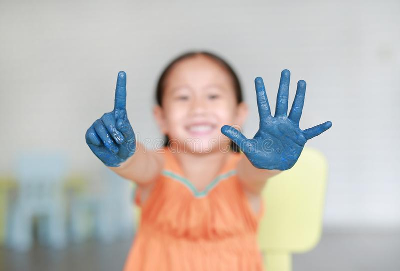 La pequeña muchacha asiática feliz con sus manos azules pintó mostrar un y cinco fingeres en sitio de los niños imagen de archivo