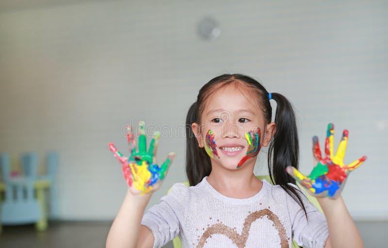 La pequeña muchacha asiática feliz con sus manos y mejilla coloridas pintó en el cuarto de niños Foco en la cara del bebé fotografía de archivo