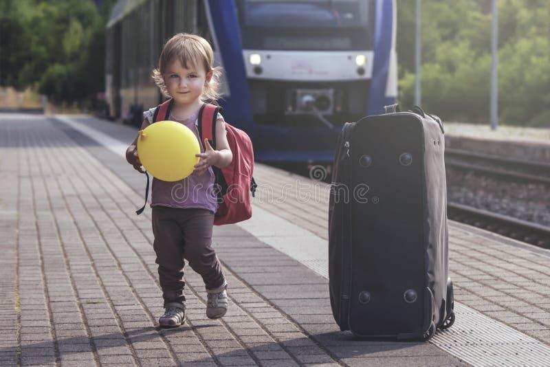 La pequeña muchacha bonita camina a lo largo de la plataforma de la estación del tr fotografía de archivo libre de regalías