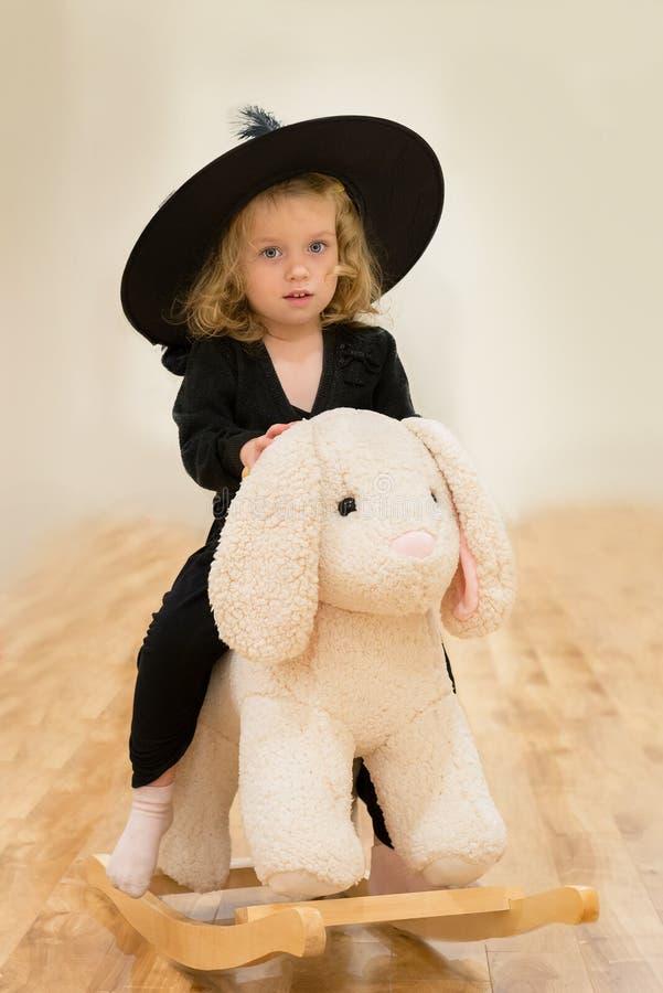 La pequeña muchacha caucásica adorable se sienta en el juguete mullido del conejito Ella está en vestido negro y sombrero negro g fotos de archivo