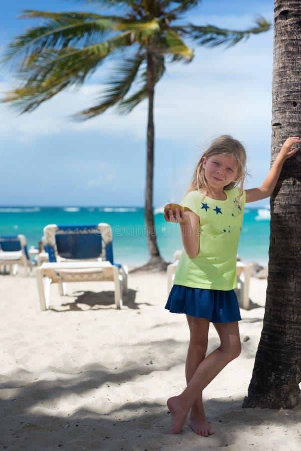 La pequeña muchacha caucásica rubia sostiene nueces en la playa del Caribe Las palmas, el océano azul y el cielo están como fondo fotografía de archivo libre de regalías