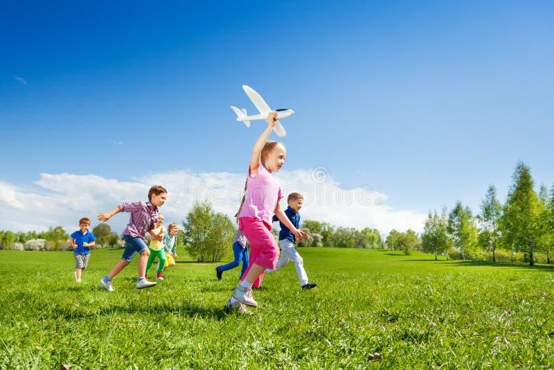 La pequeña muchacha celebra el funcionamiento del juguete y de los niños del aeroplano imágenes de archivo libres de regalías