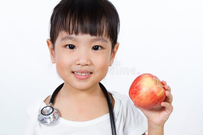 La pequeña muchacha china asiática se vistió para arriba como doctor con un Stethoscop imágenes de archivo libres de regalías