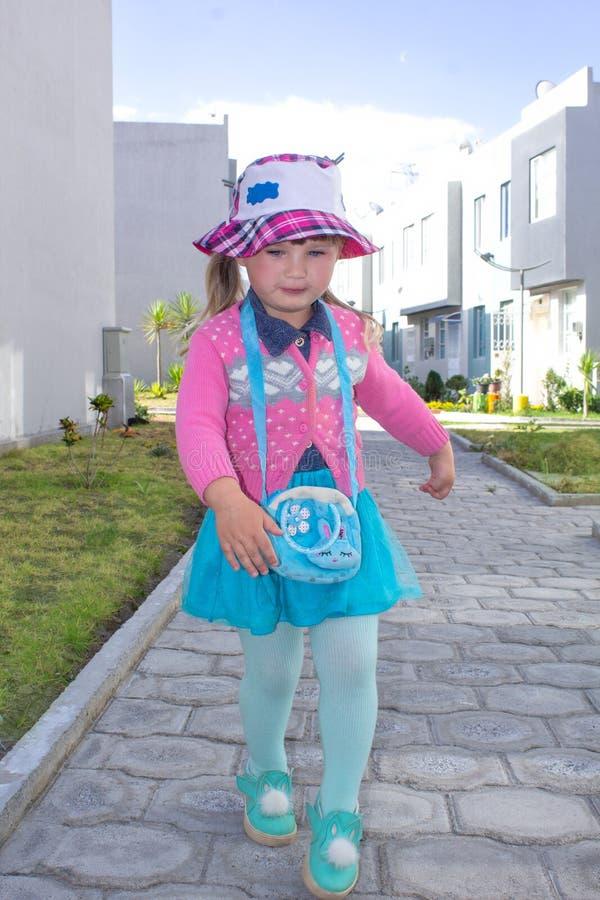 La pequeña muchacha de moda camina abajo de la calle en Panamá Árbol en campo foto de archivo libre de regalías