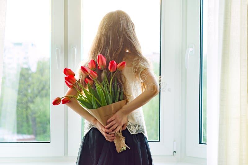 La pequeña muchacha del niño hermoso con el ramo de flores rojas de los tulipanes en casa cerca de la ventana, presenta para el d foto de archivo libre de regalías