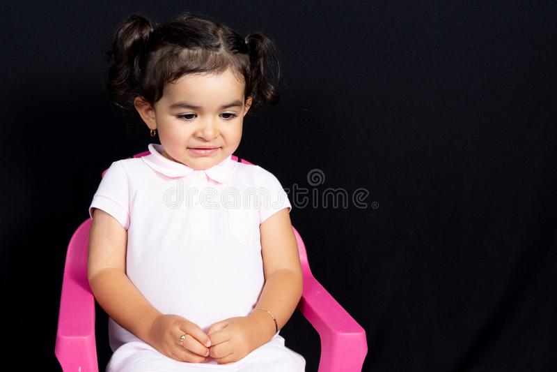 La pequeña muchacha elegante parece tímida se sienta en silla rosada en fondo negro fotografía de archivo