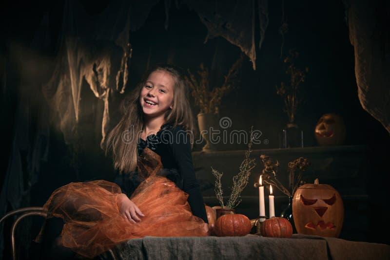La pequeña muchacha en traje de la bruja se sienta en la tabla imagen de archivo libre de regalías