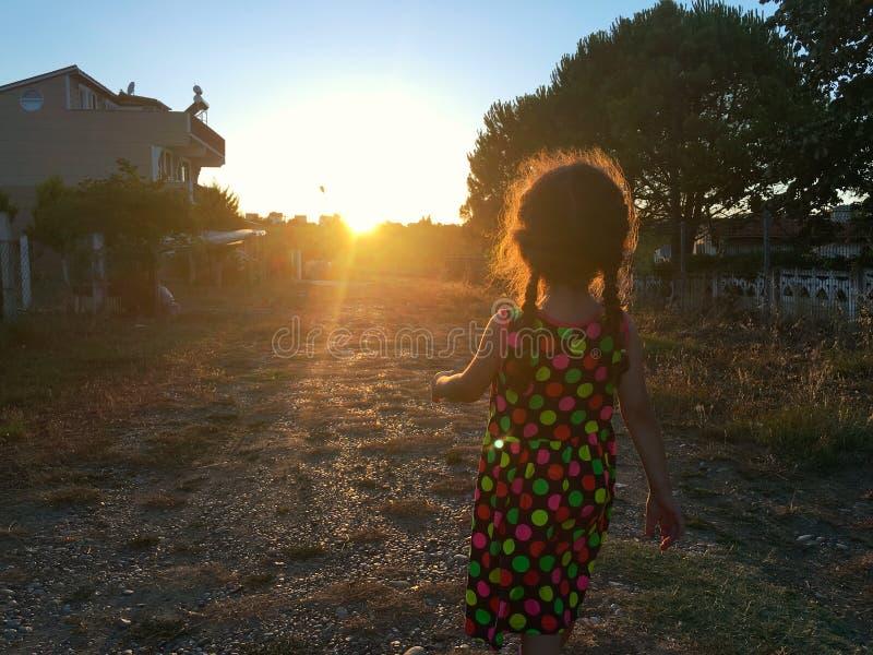 La pequeña muchacha en vestido colorido está en el campo que camina a la puesta del sol foto de archivo