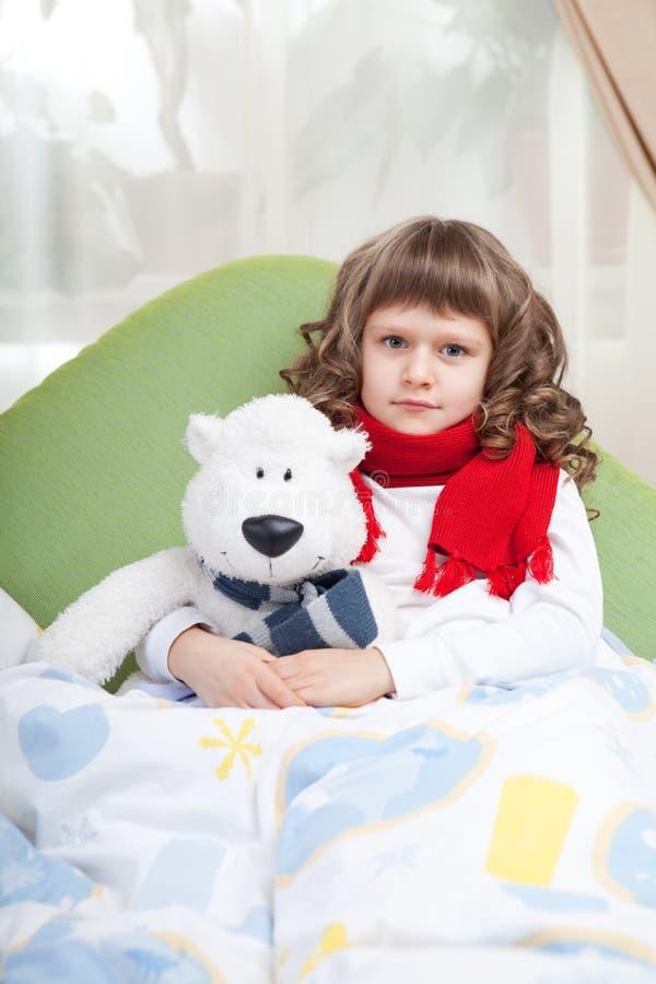 La pequeña muchacha enferma con la bufanda abraza el oso del juguete imagen de archivo
