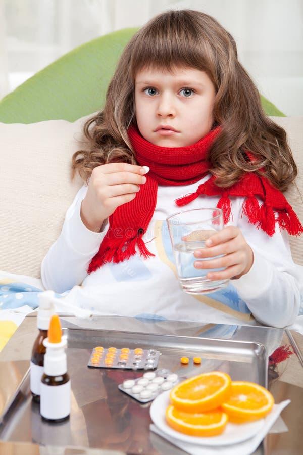 La pequeña muchacha enferma en cama está tomando la medicina imagen de archivo