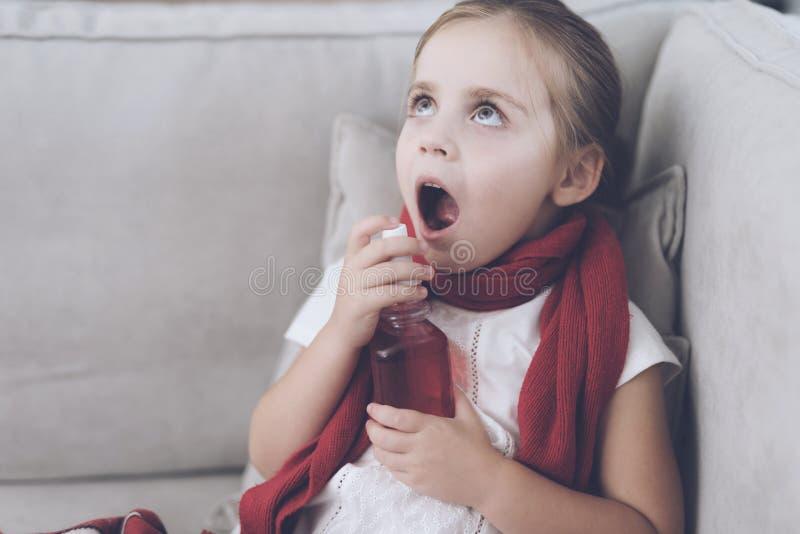 La pequeña muchacha enferma se sienta en un sofá blanco envuelto en una bufanda roja Ella salpica su garganta con un espray medic imagen de archivo
