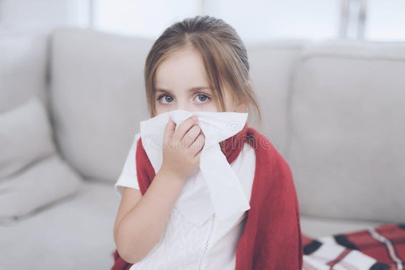 La pequeña muchacha enferma se sienta en un sofá blanco envuelto en una bufanda roja Ella sopla su nariz en una servilleta foto de archivo libre de regalías