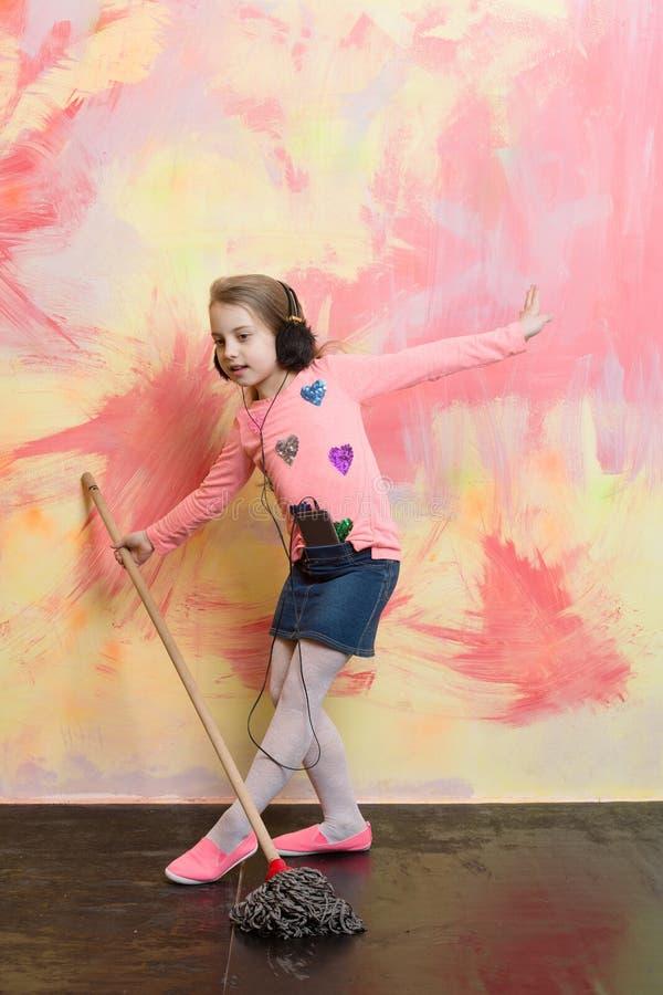 La pequeña muchacha escucha música con la fregona imágenes de archivo libres de regalías