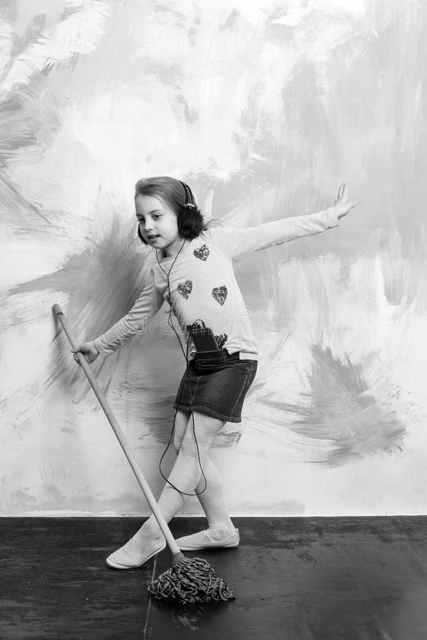 La pequeña muchacha escucha música con la fregona foto de archivo libre de regalías
