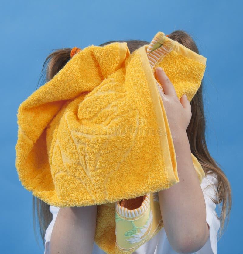 La pequeña muchacha está limpiando su cara por la toalla aislada fotos de archivo