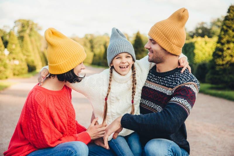 La pequeña muchacha feliz abraza a su madre y el padre, tiene la diversión junto, paseo en parque hermoso o en el camino Mirada d imagen de archivo libre de regalías