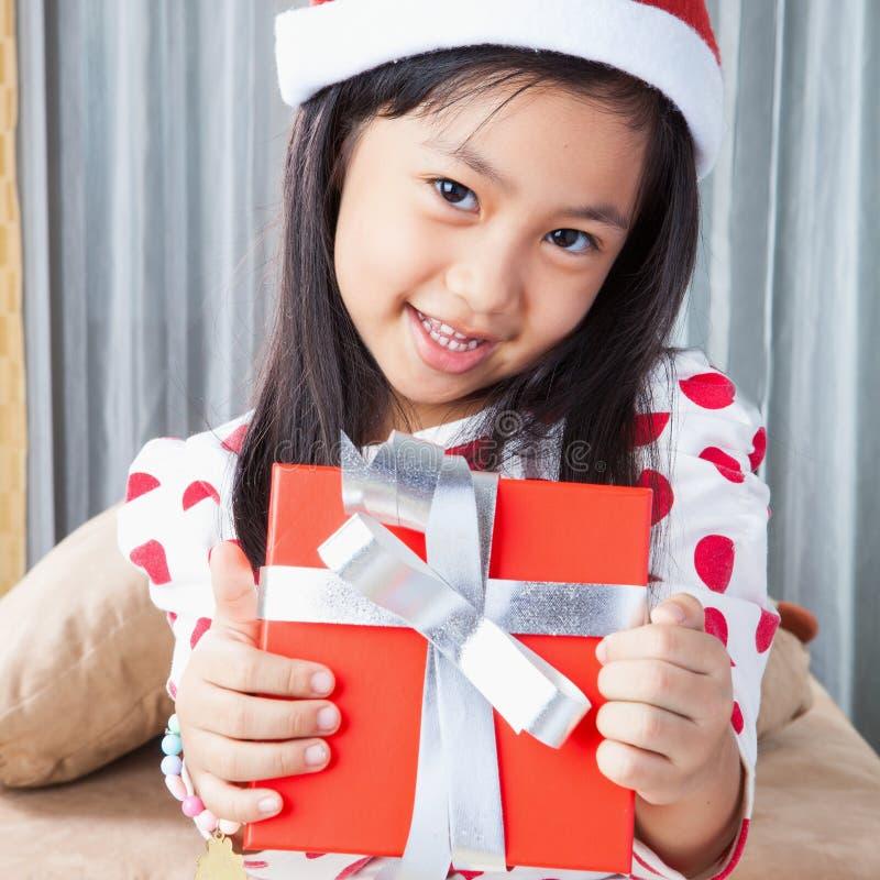 La pequeña muchacha feliz en el sombrero de Santa tiene una Navidad imagen de archivo