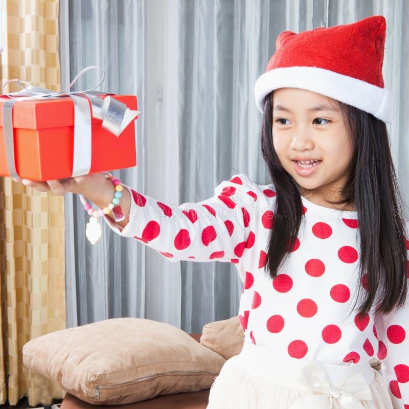 La pequeña muchacha feliz en el sombrero de Santa tiene una Navidad fotografía de archivo libre de regalías