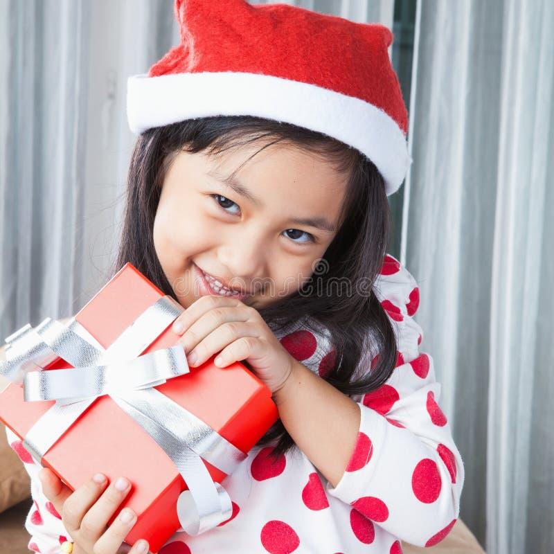 La pequeña muchacha feliz en el sombrero de Santa tiene una Navidad imagen de archivo libre de regalías