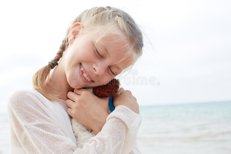 La pequeña muchacha hermosa abraza un perro graciosamente - juguete Juguete suave preferido foto de archivo