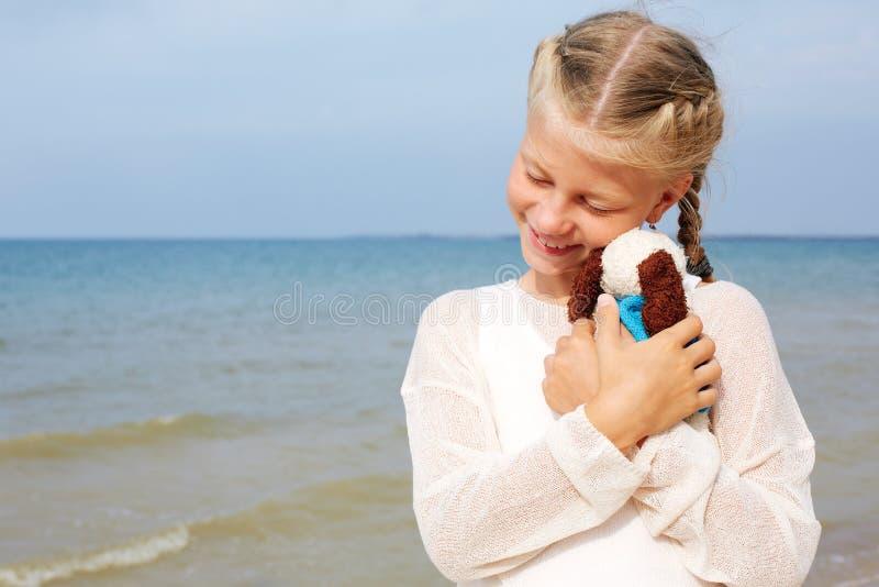 La pequeña muchacha hermosa abraza un perro graciosamente - juguete Juguete suave preferido fotografía de archivo libre de regalías