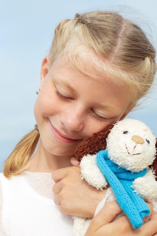 La pequeña muchacha hermosa abraza un perro graciosamente - juguete Juguete suave preferido imagenes de archivo
