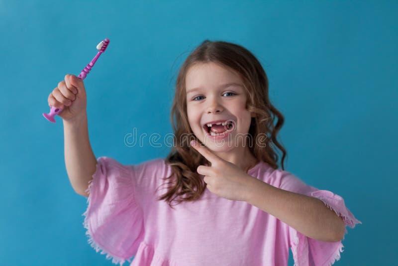 La pequeña muchacha hermosa limpia la odontología del cepillo de dientes de los dientes fotografía de archivo