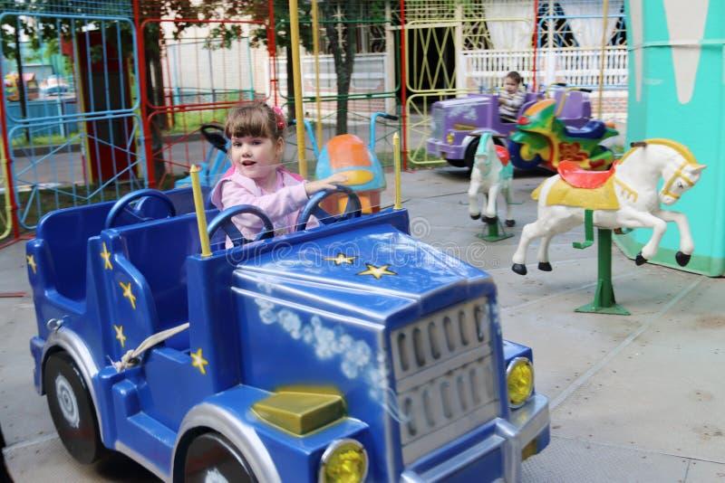 La pequeña muchacha hermosa monta en el coche del carrusel en parque de atracciones foto de archivo