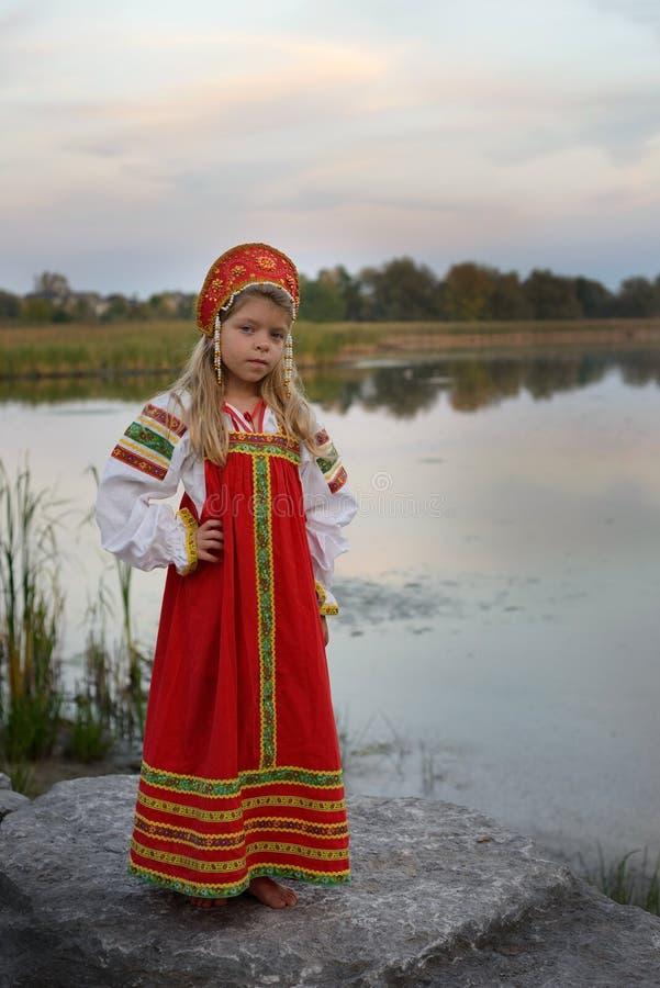 La pequeña muchacha hermosa se vistió en el traje nacional ruso en fondo natural imagen de archivo libre de regalías