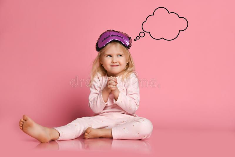 La pequeña muchacha linda alegre en pijamas se sienta en el piso en un fondo rosado en una máscara del sueño por la mañana y los  fotos de archivo