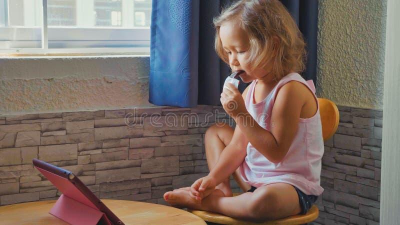 La pequeña muchacha linda del niño que mira algo en la tableta y come la paleta helada de fruta fotos de archivo libres de regalías
